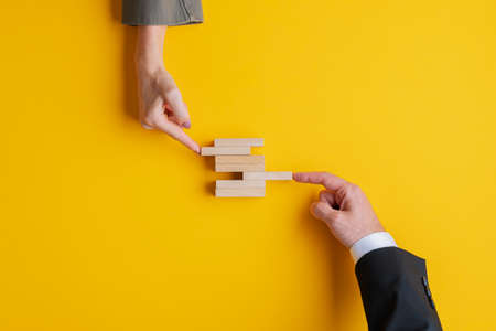 Business teamwork and cooperation concept - hands of businessman and businesswoman pushing wooden peg in a stack of them. Over yellow background, with copy space. Archivio Fotografico