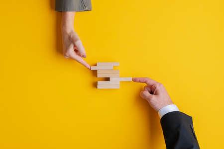 Business Teamwork und Kooperationskonzept - Hände von Geschäftsmann und Geschäftsfrau, die Holzpflöcke in einen Stapel schieben. Auf gelbem Hintergrund mit Kopienraum. Standard-Bild