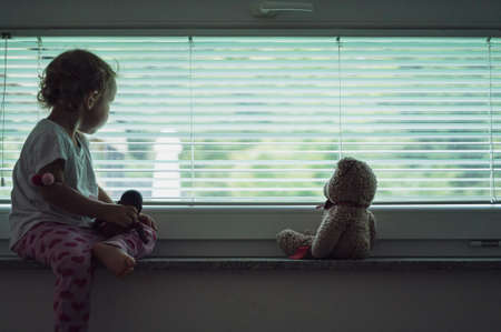 Toddler girl sitting on window shelf with her teddy bear looking out the window with blinds on it. Conceptual image of child abuse and abandonment.