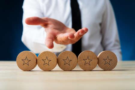 Ręka biznesmena przedstawiająca pięć drewnianych wyciętych kółek z gwiazdami na nich w konceptualnym obrazie luksusu i bogactwa.