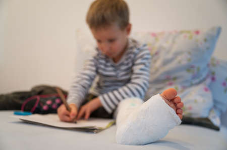 Vista de ángulo bajo de un niño pequeño con yeso en la pierna, dibujo con lápices de colores.