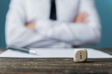 Businessman sitting at his desk with pen and paper in front of him and a dice wit letter i on it. Conceptual image of service and information. Reklamní fotografie