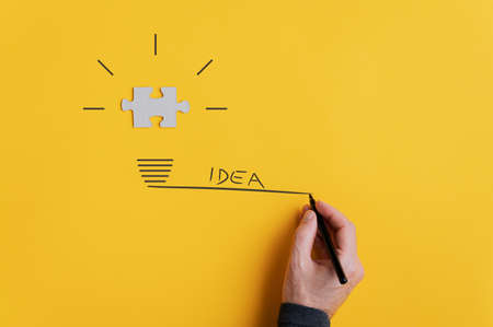 Male hand drawing light bulb with the word idea to the side. Over yellow background. Imagens