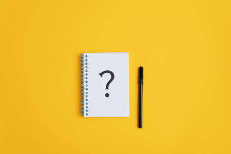 Question mark drawn on notepad with black marker lying next to it. Over yellow background with copy space. 版權商用圖片