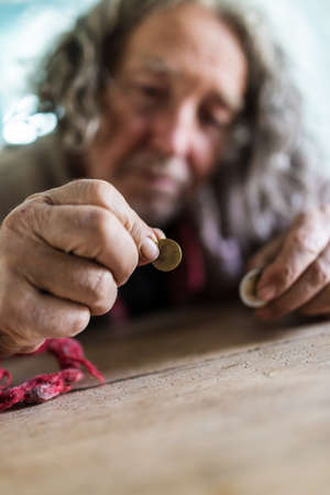 Conceptual image of poverty and personal crisis - senior man in torn sweater counting Euro coins.