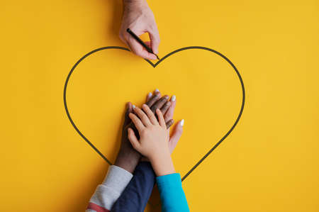 Top view of a man drawing heart shape around stacked hands of his family - fife and two kids, one caucasian one black in a conceptual image. Over yellow background