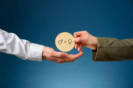 Gender equality conceptual image - female hand giving her male partner a wooden cut circle with male and female signs on it.