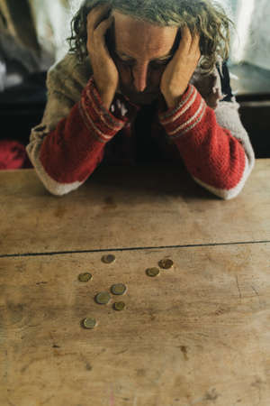 Worried senior man leaning his head on his hands with a few Euro coins on desk in front of him. Conceptual image of personal poverty and crisis. Stock fotó