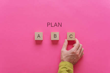 Male hand choosing plan C out of options A, B and C. Over pink background. Stock Photo