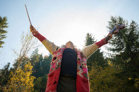 Low angle view of homeless senior violin player in torn sweater, celebrating life with hands lifted in the air. Banque d'images