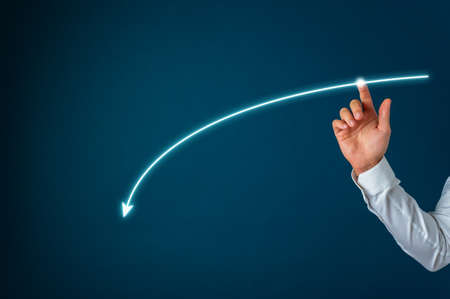 Hand of a businessman drawing a glowing arrow falling downwards on a virtual interface. Over blue background.