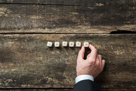Businessman placing six wooden dices with contact and communication icons on them on a rustic wooden background.