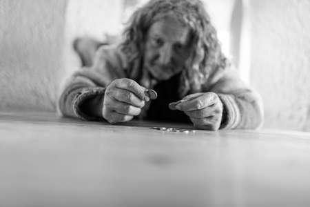 Greyscale image of a senior homeless man counting his last euro coins in a conceptual image of poverty and charity. Stock Photo