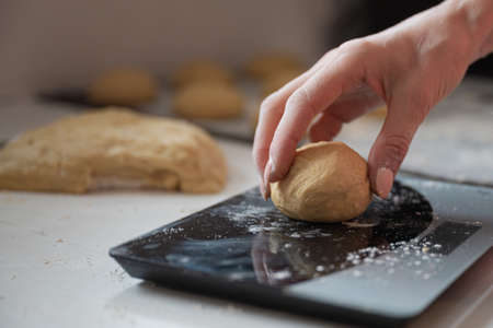 Closeup of female hand weighing home made pastry dough ball.