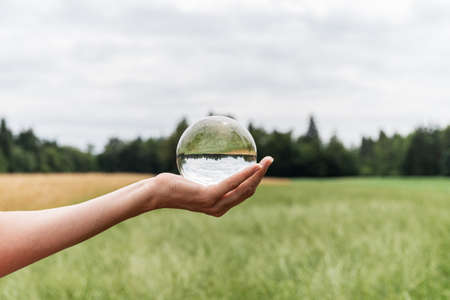 Female hand holding crystal ball in nature with beautiful green meadow and golden wheat field reflecting in the sphere.