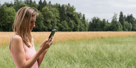 Profile view of young woman browsing on her mobile phone while on a walk outside in summer nature.
