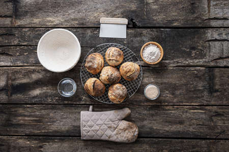 Top view of still life setting with freshly baked homemade sourdough bread buns, bowl of flour, kitchen mitten, jar of starter yeast, cup of water, dough cutter and braided dough basket.