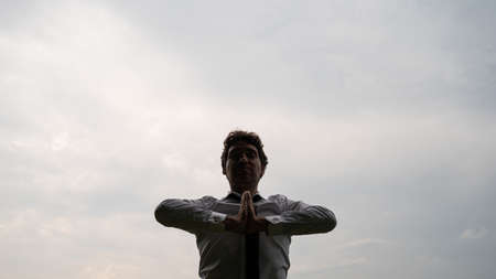 Low angle view of young businessman relaxing with his hands joined in front of his chest, standing under grey sky.