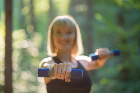 Young woman exercising with small hand weights outside in beautiful green forest. Focus to the hand. Фото со стока - 147056194