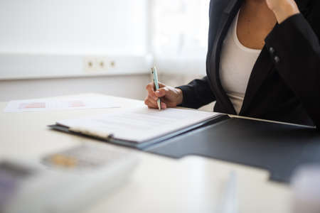 Closeup view of businesswoman sitting at her desk signing a document or contract in a folder.