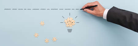 Light bulb made of puzzle pieces and hand of a businessman writing crucial words of business success above it.