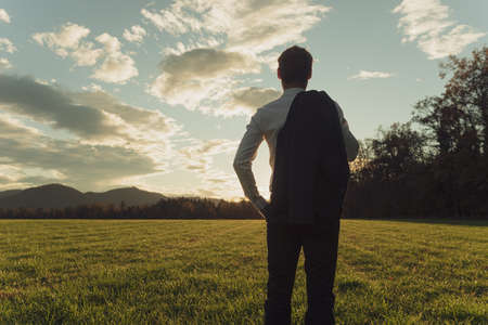 View from behind of a young businessman with his jacket over the shoulder standing in beautiful autumn meadow looking into the distance.
