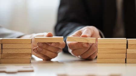 Closeup view of businessman and businesswoman making a bridge of wooden blocks between two stacks of them in a conceptual image of merger and cooperation.