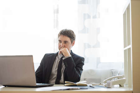 Young businessman in a suit sitting at his office desk working on laptop computer with a thoughtful face.