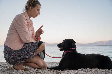 Young woman kneeling down to give command to her black shepherd dog on beautiful pebble beach. 写真素材