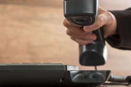 Closeup view of businessman hand picking or hanging up a black landline telephone handset.
