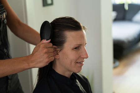 Young woman sitting at hairdresser salon as the stylist brushes her wet hair.