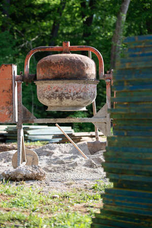 Cement mixer standing in construction site next to a pile of wooden planks. Imagens