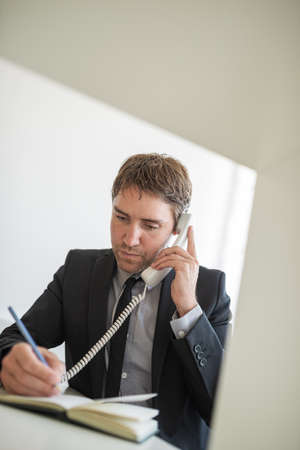 Handsome young businessman sitting at his office desk talking on white landline phone and making notes.