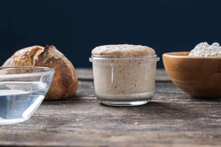 Still life setting with jar of sourdough starter yeast, cup of water and flour and home made bread bun.