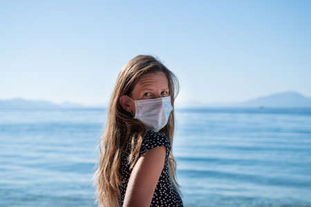 Young woman with long brown hair wearing medical protective mask while standing next to a beautiful blue sea. Imagens