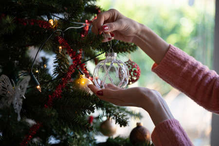 Closeup view of a woman with seasonal manicure hanging shiny transparent holiday bauble on christmas tree.