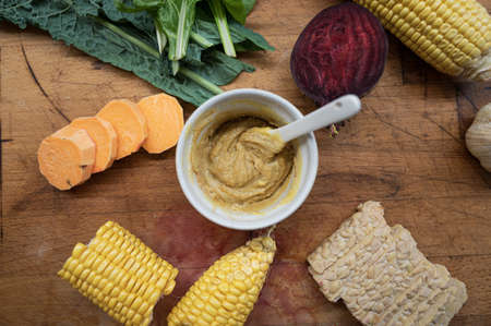 Top view of vegan sauce or dip in a cup in the middle of various autumn vegetables such as corn, beetroot, sweet potato and tempeh protein.