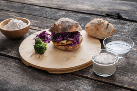 Still life setting with home made delicious vegan burger, sourdough starter yeast and flour.