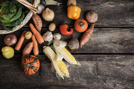 Top view of various autumn vegetables such as sweet potato, corn, carrots, squash, onions, scattered out of a wicker basket onto wooden boards.