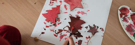 Top view of a child coloring wooden cut holiday trees red making seasonal ornaments. Imagens