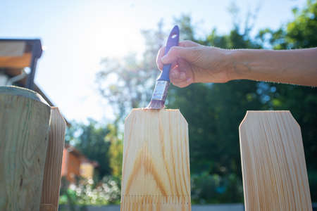 Low angle view of female hand painting new wooden fence with a transparent protective varnish.