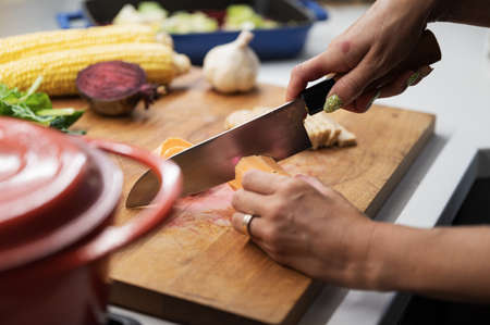 Female hands cutting sweet potato on a wooden kitchen board full of various autumn vegetables. Imagens