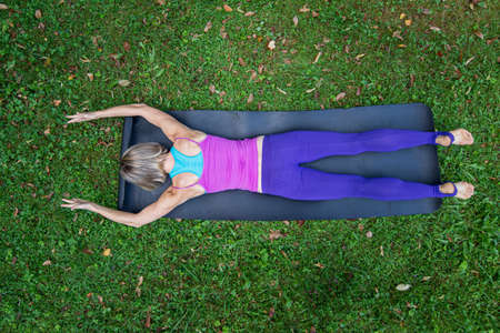 Top view of a young fit woman lying with her belly on an exercise mat in a grass practicing pilates.
