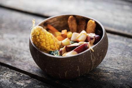 Coconut bowl full of balanced organic meal serving full of vegan variety foods.