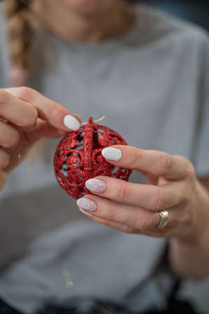 Closeup view of a woman with pink winter manicure tying a golden string on shiny red holiday bauble. Imagens