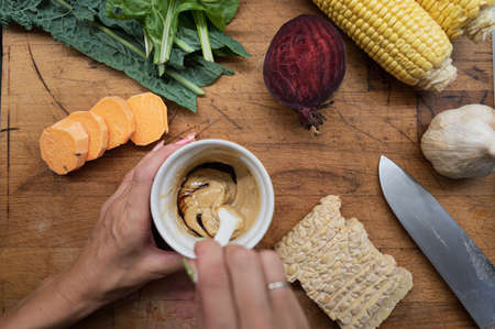 Top view of a woman making vegan dressing in a cup on wooden cutting board full of various autumn vegetables and tempeh protein.