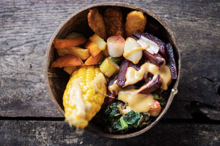 Top view of organic vegan meal with corn, tempeh protein and vegetables served in coconut buddha bowl.