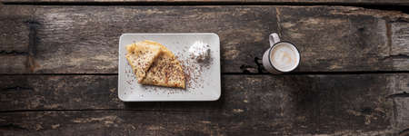 Wide view image of home made vegan crepe folded and served with whipped cream and chocolate sprinkles with a cup of coffee. Imagens