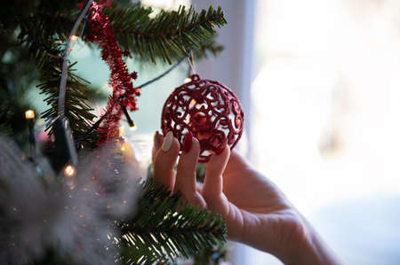 Closeup view of female hand with holiday manicure holding shiny red holiday bauble hanging from a christmas tree with lights.