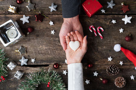 Top view of female hand in her partners palm holding marble made heart shape in the center of christmas setting.